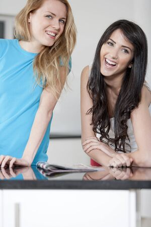 Two young woman chatting and sharing a magazine photo