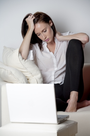 Young woman on a sofa at home expressing concern and worry while using a laptop