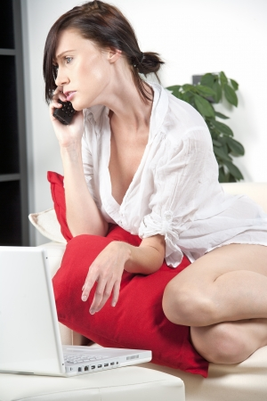 home phone: Young woman in white shirt expressing concern and worry on the phone