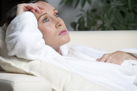 bath robe: Young woman in a white bath robe relaxing on a sofa at home Stock Photo