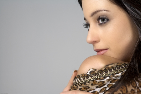 Beautiful young woman with dark hair wearing an animal print dress