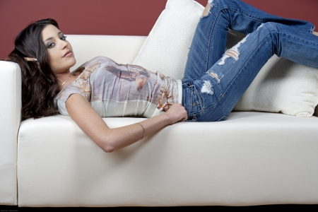Beautiful young woman relaxing on a sofa at home photo