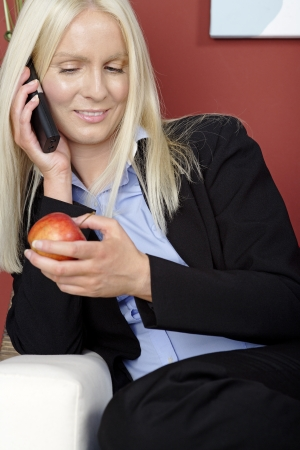 Young woman holding an apple and phone while relaxing at home photo