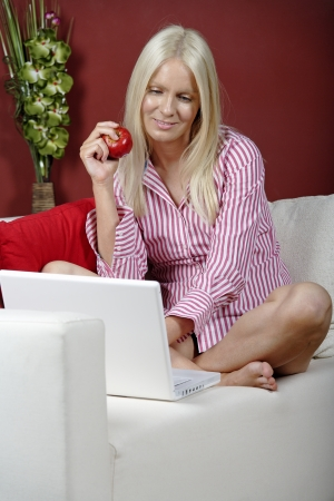 Young woman on her sofa at home using a laptop computer Stock Photo - 14324802