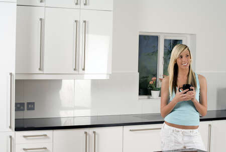 Young woman relaxing in kitchen, with hot drink photo