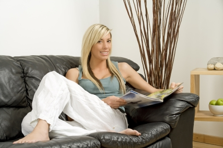 Young woman reading a magazine on the sofa at home photo
