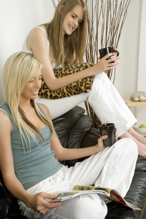 Two friends chatting and relaxing at home photo