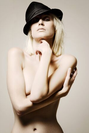 half nude: Young demale model wearing a black hat over one eye.  Her upper body is covered by both arms.