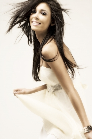 Young female model with flowing dark hair, wearing a long white dress. Stock Photo - 14318909