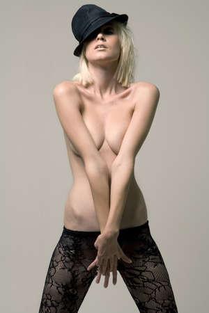 femme noire nue: Jeune mod�le f�minin dans le chapeau noir inclin� couvrant sa poitrine avec les deux bras.