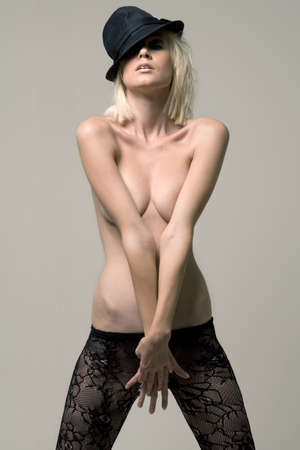 hat nude: Young female model in tilted black hat covering her chest with both arms.