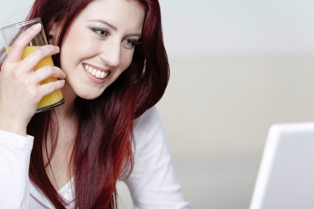 Beautiful young woman using a laptop at home with a fresh glass of Orange juice. Stock Photo - 14424922