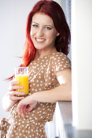 Happy smiling young woman standing by a window at home with a fresh glass of Orange juice. Stock Photo - 14425405