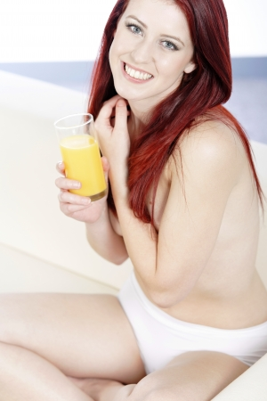 Beautiful woman drinking fresh Orange juice on her sofa at home photo