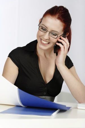 Beautiful young woman talking on her mobile phone at work Stock Photo - 14425323