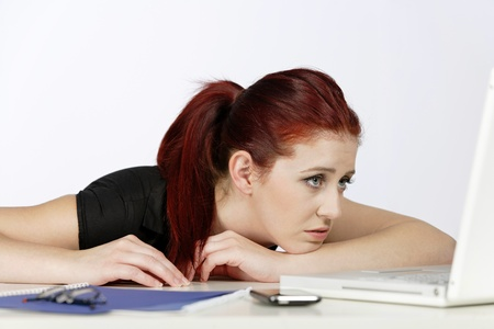 preocupacion: Mujer profesional que muestra su preocupaci�n por el trabajo usando su computadora port�til Foto de archivo