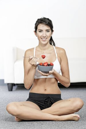 beautiful young woman in fitness clothes eating fresh fruit from a bowl at home photo