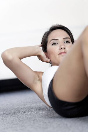 Beautiful young woman doing sit ups at home on the floor Stock Photo - 14761253