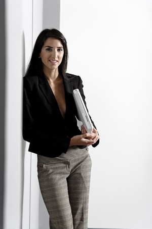 Professional working woman in corporate business suit holding a laptop computer Stock Photo - 14761595