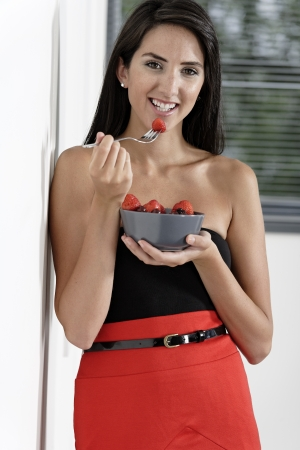 pencil skirt: Beautiful sexy young woman in red pencil skirt eating breakfast fruit salad Stock Photo