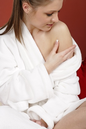 bath robe: Young woman sat on her sofa at home weaing a white bath robe