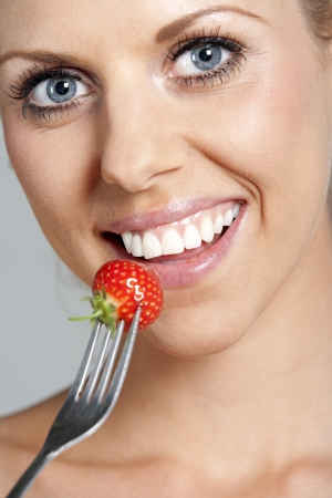 Beautiful young woman eating fresh summer berries photo