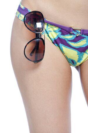 bikini bottom: Imagen recortada de una cadera womans que muestran una parte inferior del bikini con gafas de sol Foto de archivo