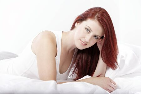 Young woman lying on her white bed at home relaxing Stock Photo - 15441316