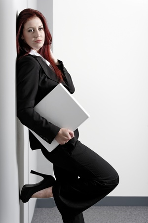 Professional business woman holding a white laptop at work photo