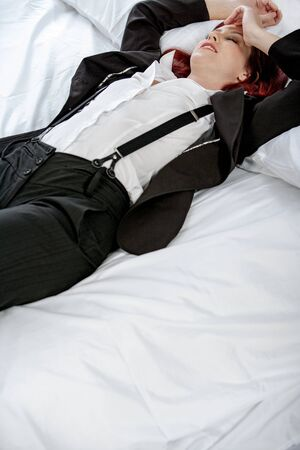 Professional business woman lying on a bed after a long day in the office nursing a headache. Stock Photo - 15435835