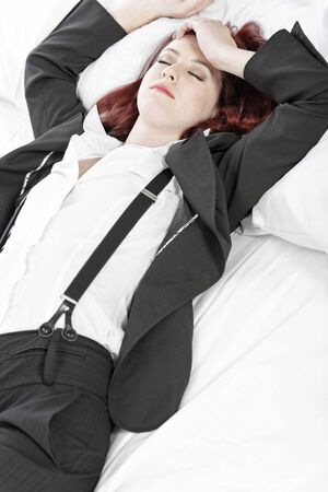 Professional business woman lying on a bed after a long day in the office nursing a headache. photo