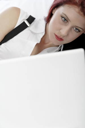Professional business woman lying on a bed after a long day in the office still working on the laptop computer Stock Photo - 15440926