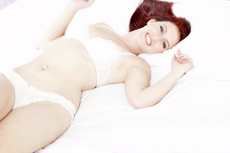 Attractive young woman lying on her bed in her underwear at home Stock Photo - 15440911
