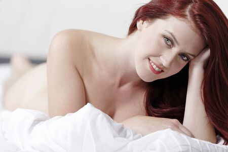 Beautiful young woman  on her bed at home relaxing on the white covers Stock Photo - 15440897
