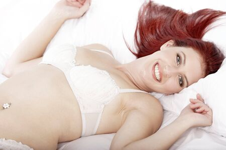 Attractive young woman lying on her bed in her underwear at home Stock Photo - 15440865