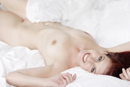woman body: Beautiful young woman on her bed at home relaxing on the white covers Stock Photo