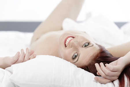 Beautiful young woman  on her bed at home relaxing on the white covers Stock Photo - 15440924