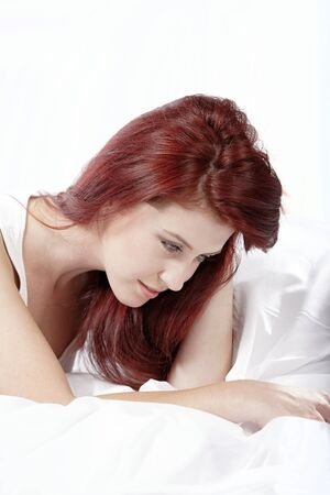 Young woman lying on her white bed at home relaxing Stock Photo - 15465873