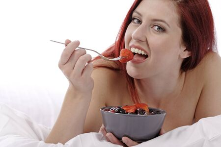 Attractive young woman on her bed at home eating fresh fruit for breakfast photo