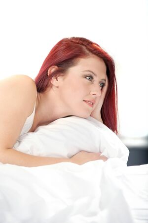Young woman lying on her white bed at home relaxing Stock Photo - 15441543