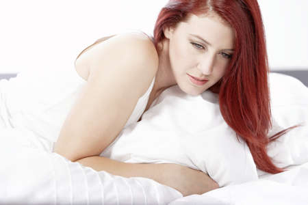 Young woman lying on her white bed at home relaxing Stock Photo - 15465869