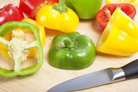 Selection of red green and yellow peppers sliced up on a chopping board Stock Photo - 15572112