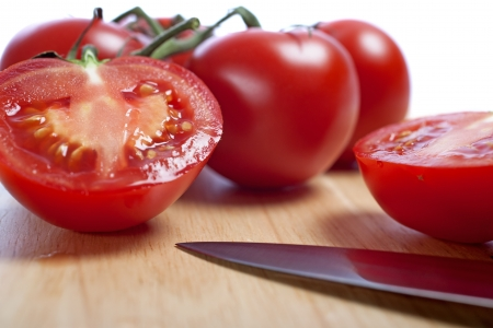 Fresh tomatoes being sliced on a wooden chopping board with knife Stock Photo - 15572123
