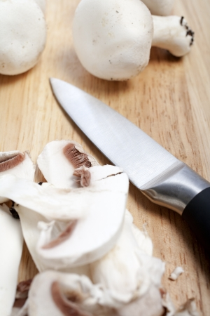Fresh organic mushrooms being sliced on a wooden chopping board Stock Photo - 15572078