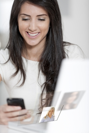 Young woman chatting with friends displaying a social media concept. Stock Photo - 16216616