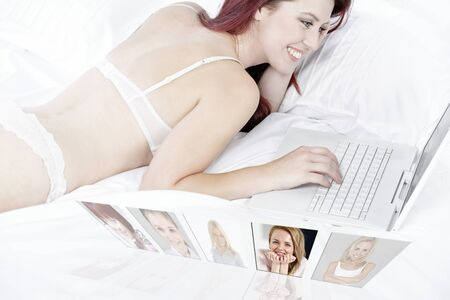 Woman lying on her bed chatting with friends online. photo
