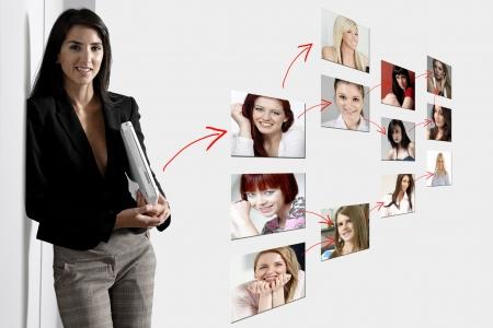 networking people: Mujer joven apoyado contra una pared blanca que sostiene un ordenador port�til blanco que muestra el concepto de la conexi�n de red. Foto de archivo