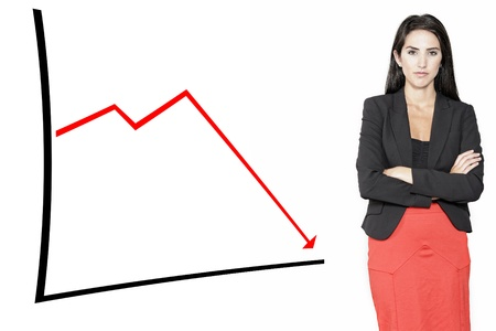 Stern professional woman displaying a concept of decline on a chart Stock Photo