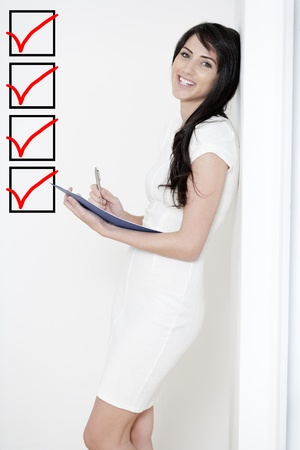 Young woman in white dress leaning against a white wall holding a blue folder while ticking off a checklist