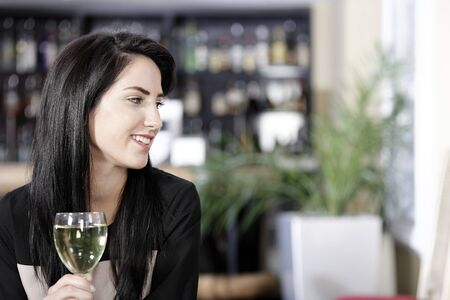 Attractive young woman enjoying a glass of white wine in a wine bar. Stock Photo - 16217641